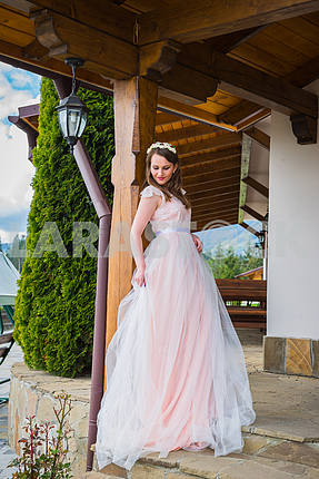 Beautiful bride in long dress stands at the door and looks outside. Tulle Dress  Lovely girl