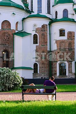 The guy and the girl have a rest from the ancient walls of St. Sophia Cathedral in Kiev in 2012