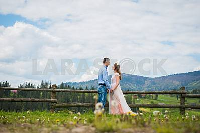 Beautiful young wedding couple holding each other with hands, with magnificent forest hills as background. blue sky with the coulds. wedding walk on nature