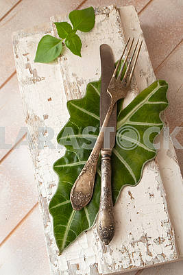 Fork and knife on wooden board with fresh basil leaves, vintage image