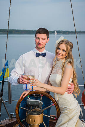 Happy bride and groom drinking champagne on a sailing yacht. happy together.  The steering wheel of the yacht.