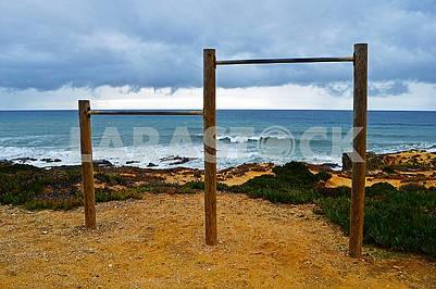 Гімнастична перекладина на пляжі на тлі темно бурхливого неба