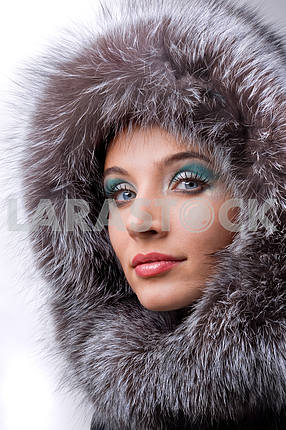 Portrait of the beautiful young woman with a fur hood