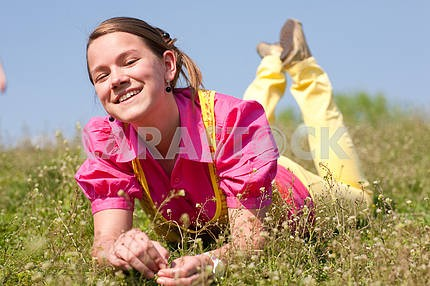 Pretty smiling girl relaxing on green meadow full of flowers. So