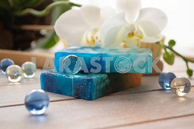 Sea salt, natural soap and orchid flower on wooden background. Aroma spa set