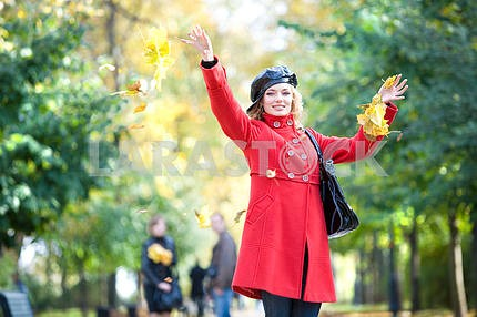 Happy woman in red throwing leaves in the air