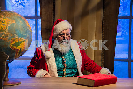 Santa Claus sitting in his chair at his desk.
