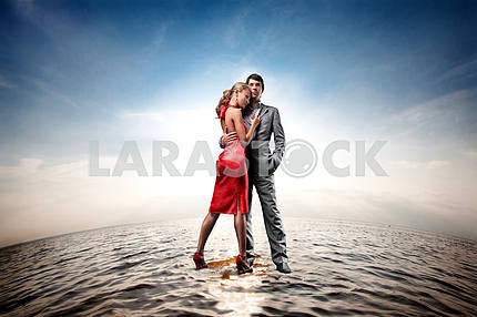 Happy young couple standing on water