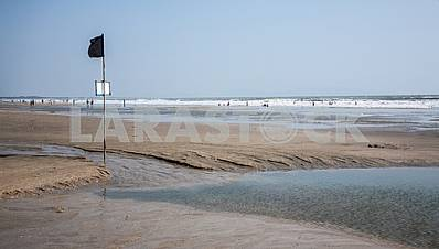 Deserted beach with a black flag on a pole