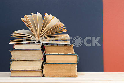 Stack of hardback books on blue cloth. Back to school. Copy space