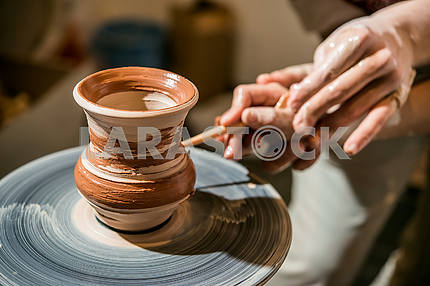 The potter on the potter's wheel teaches the child to make a pitcher from clay