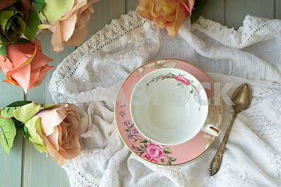 Vintage tea cup with gold rim. White linen tablecloth. Pastel roses, top view