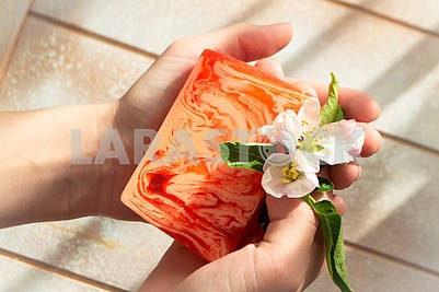 Closeup on young woman hands with organic homemade soap and tender flowers
