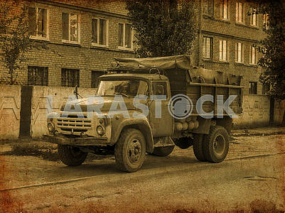 An old dump truck truck stands on the side of the road black and white photo.